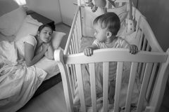 Black and white portrait of tired young mother falling asleep nex tto sleepless baby boy. Black and white portrait of tired mother falling asleep nex tto royalty free stock photography