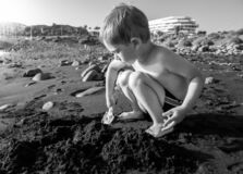 Black and white portrait of little toddler boy digging sand on the ocean beach at sunset