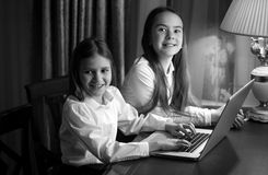Black and white portrait of two sisters using laptop. Black and white portrait of two little sisters using laptop Royalty Free Stock Image