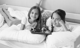Black and white portrait of two sisters lying in bedroom and using digital tablet. Black and white portrait of two smiling sisters lying in bedroom and using Stock Photography
