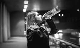 Black and white portrait of woman drinking whiskey at night on s. Closeup black and white portrait of woman drinking whiskey at night on street Stock Photography
