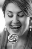 Black and white portrait of woman looking at lollipop Stock Images
