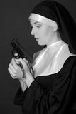 Black and white portrait of woman nun holding gun Stock Images