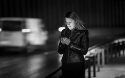 Black and white portrait of woman typing message on street at ni Royalty Free Stock Image