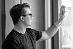 Black and white portrait of young handsome caucasian man washes the window with sponge. Dark curly hair, glasses, smart look, litt stock image