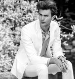 Black-white portrait of young handsome fashionable man in white suit against nature background Royalty Free Stock Photos