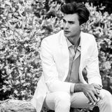 Black-white portrait of young handsome fashionable man in white suit against nature background Stock Image