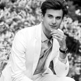 Black-white portrait of young handsome fashionable man in white suit against nature background Royalty Free Stock Images