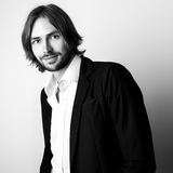 Black-white portrait of young handsome long hair man against studio background Royalty Free Stock Photography
