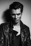 Black and white portrait of young man in leather jacket stock image