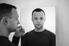 Black and white portrait of young man with mirror. Black and white portrait of young adult European man standing near white wall with mirror royalty free stock photography