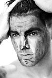 Black and white portrait of a young man with streaks of paint on face . fantasy art of makeup Royalty Free Stock Images