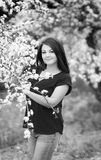 Black and white portrait of a young woman holding a brunch of blossoming plum tree in garden, happily smiling Stock Photo