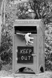 Black and white postal box with ghoul hand emerging. Halloween mail box with purple pink monster hand protruding from the slot and large keep out sign Stock Photos