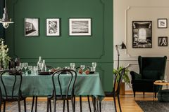 Black and white posters on wall of stylish dining room interior with log table with wine glasses, plates and cones. Black and white posters on green wall of royalty free stock photos
