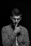 Black and white postudio portrait of brutal bearded man touching