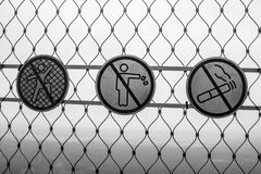 Black and white prohibiting signs on the grid 001. Black and white prohibiting signs on the grid Royalty Free Stock Photography
