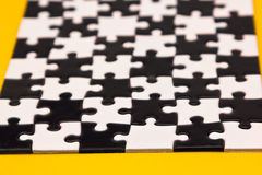 Black and white puzzles. On a yellow background Royalty Free Stock Image