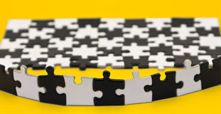 Black and white puzzles. On a yellow background Stock Images