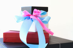 Black white and red gift box with blue and pink ribbon bow Stock Image