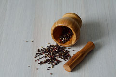 Black, white, red, green peppercorns in w wooden mortar Royalty Free Stock Images