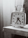 Black and white retro alarm clock with bells on the table Royalty Free Stock Image