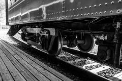 Train Wheels on a Vintage Passenger Car. Black and White retro look of the undercarriage of a vintage rail car from a bygone era Stock Photo