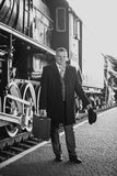 Black and white retro photo of man in suit waiting for train Stock Images