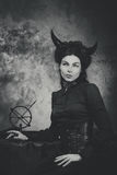 Black and white retro photo, woman demon, devil. Girl with horns, effect of toning Stock Images