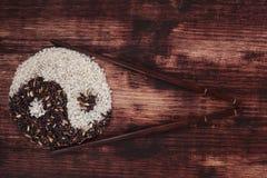 Black and white rice forming a yin yang symbol. Royalty Free Stock Image