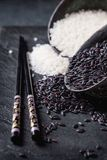 Black and white rice. In old metal china bowls with black chopsticks over black slate background Stock Image