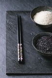 Black and white rice. In old metal china bowls with black chopsticks over black slate background Stock Photography