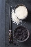 Black and white rice. In old metal china bowls with black chopsticks over black slate background. Top view Royalty Free Stock Photo