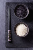 Black and white rice. In old metal china bowls with black chopsticks over black slate background. Top view Stock Photography