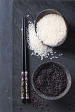 Black and white rice. In old metal china bowls with black chopsticks over black slate background. Top view Stock Photo