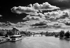 Black and white river scene. Dramatic clouds in the sky above the Elblag River with a tourist boat moored to the left and the city of Elblag, Poland, in the Royalty Free Stock Photography