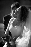 Black and white romantic portrait of groom kissing bride in chee Stock Images