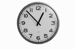 Black and white round wall clock shows almost one o`clock. Isolated on white background Royalty Free Stock Photos