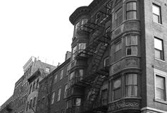 Black and white round windows. Round corners, zig zagging fire escape and aged copper spotlight this old apartment building in the beacon hill area of boston Royalty Free Stock Photos