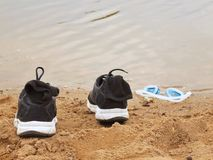 Black and white running shoes and swimming glasses on the orange sand of lake bank. Stock Image