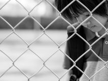 Emotions concept - sadness, sorrow, melancholy. Black and white sad boy behind fence mesh netting. Emotions concept - sadness, sorrow, melancholy royalty free stock photography