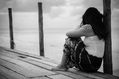 Black and white of Sad and lonely woman sitting alone. On a the wooden bridge over the sea stock photography
