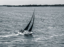 Black and white sailboat navigating stormy waters. Black and white sailboat navigating through stormy waters Stock Images