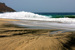 Black and white sand beach Stock Images