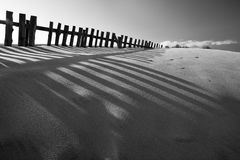 Black and white sand dune with fences stock photos