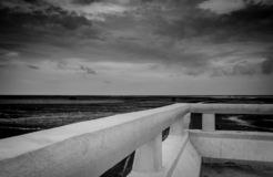 Black and white scene of mud beach at tide with grey sky and clouds. Perspective view from concrete bridge. Depressed, hopeless. Despair, grief, lament, sad royalty free stock photo