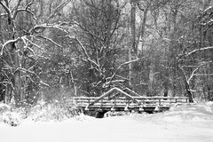 Black and white scenic image of snow covered bridge in woods. Royalty Free Stock Images