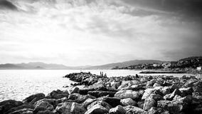 Black and white seascape of cannes rocky beach stock photography
