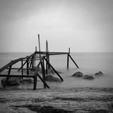 Black and white seascape with destroyed pier. Destroyed pier. Black and white seascape. Milk water. Photography with long exposure royalty free stock images