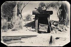 Black and White Sepia Vintage Photo of Goldfield Gold Mine old entrance to gold mine shaft with trolley. And rails leading inside, surrounded by cactus and old stock photo